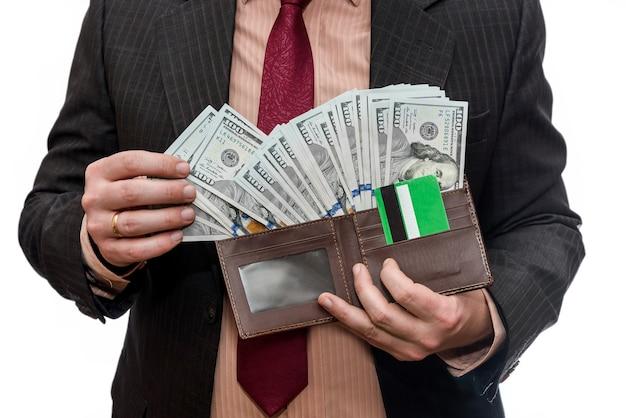 Homem de terno segurando carteira com notas de dólar e cartão de crédito