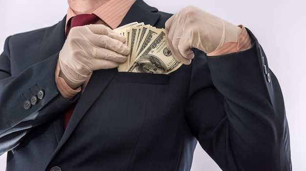Homem de terno segurando dinheiro dólares 100 contas em luvas médicas para segurança. crise do coronavírus. covid-19