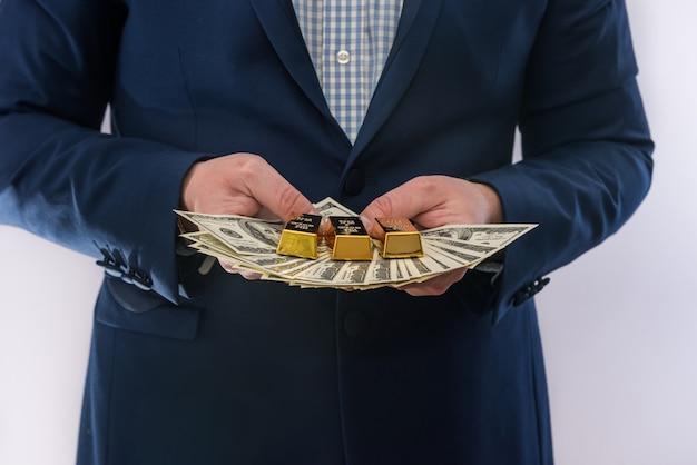 Homem de terno segurando notas de dólar e uma barra de ouro