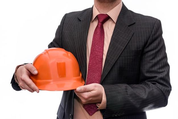 Homem de terno segurando um capacete laranja isolado na parede branca