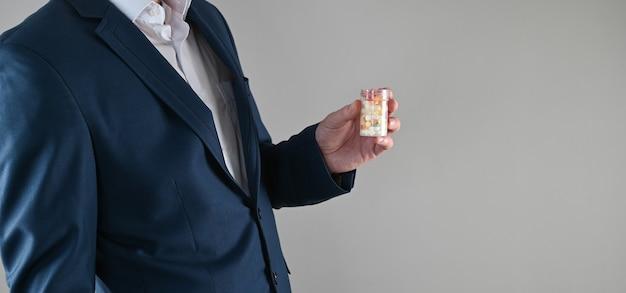 Homem de terno segurando um monte de comprimidos na mão, conceito de estresse no trabalho