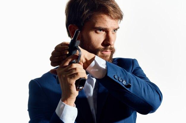 Homem de terno segurando uma arma de detetive crime isolado fundo. foto de alta qualidade