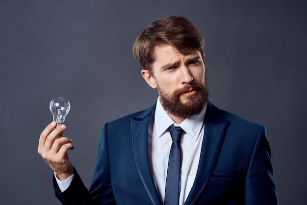Homem de terno segurando uma lâmpada, ideia de inovação de sucesso