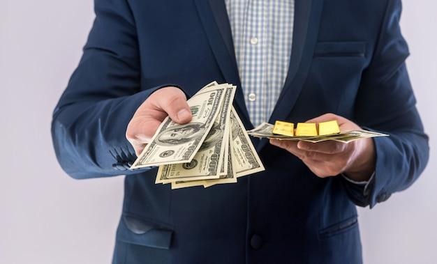 Homem de terno segurar dinheiro notas de dólar e barra de ouro. sucesso nos negócios