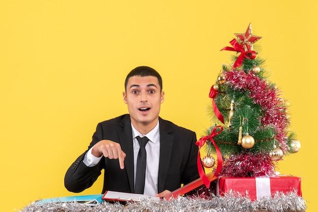 Homem de terno sentado à mesa apontando com o dedo, documento, árvore de natal e presentes