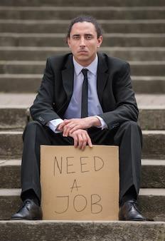 Homem de terno sentado nas escadas com sinal.