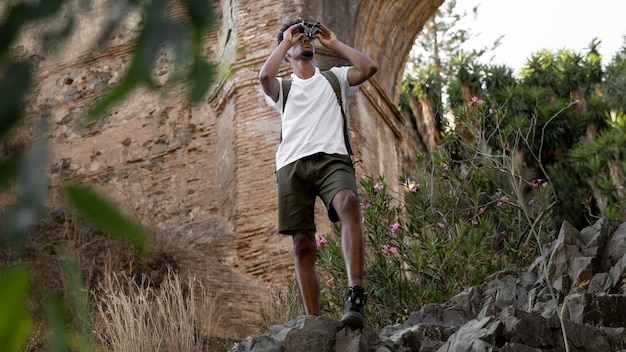 Homem de tiro completo com binóculo na natureza