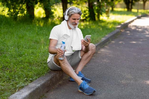 Homem de tiro completo, segurando o telefone