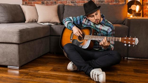 Homem de tiro completo tocando violão