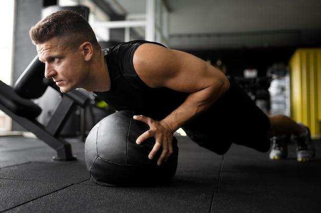 Homem de tiro completo treinando com bola