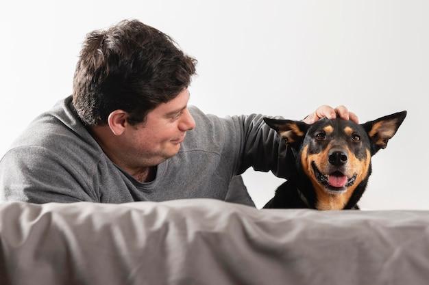 Homem de tiro médio acariciando cachorro sorridente