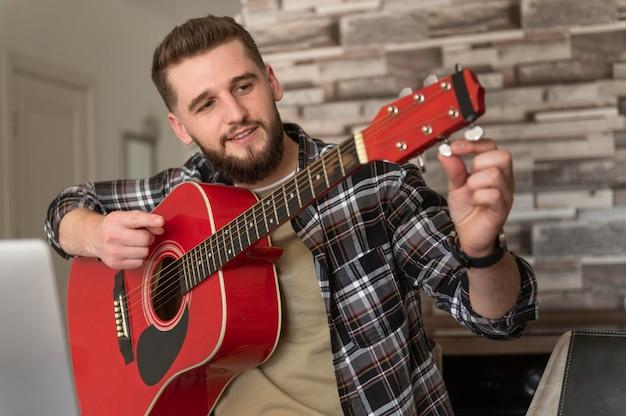 Homem de tiro médio afinando guitarra