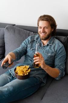 Homem de tiro médio assistindo tv em casa