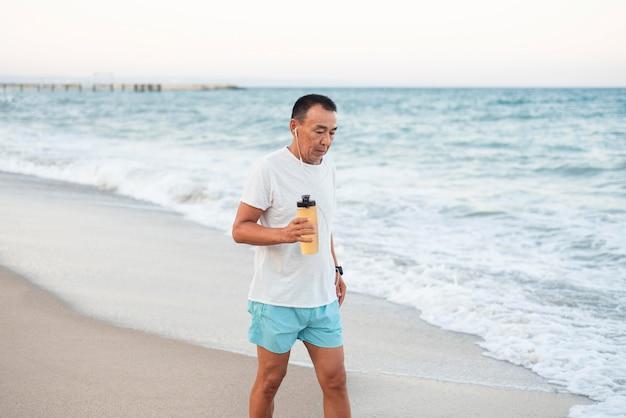 Homem de tiro médio caminhando na praia
