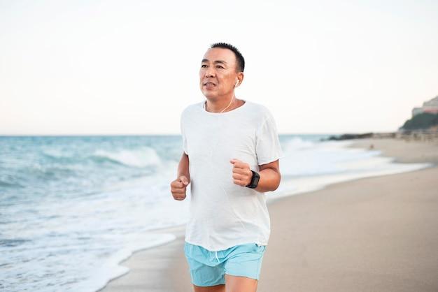 Homem de tiro médio correndo na costa
