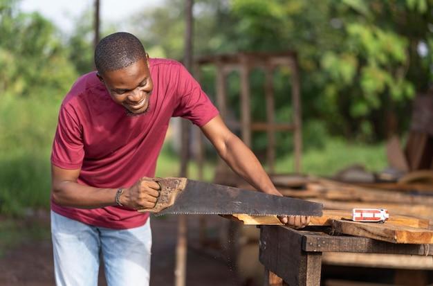Homem de tiro médio cortando madeira com serra manual