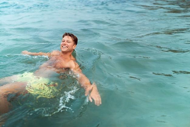 Homem de tiro médio curtindo o tempo à beira-mar