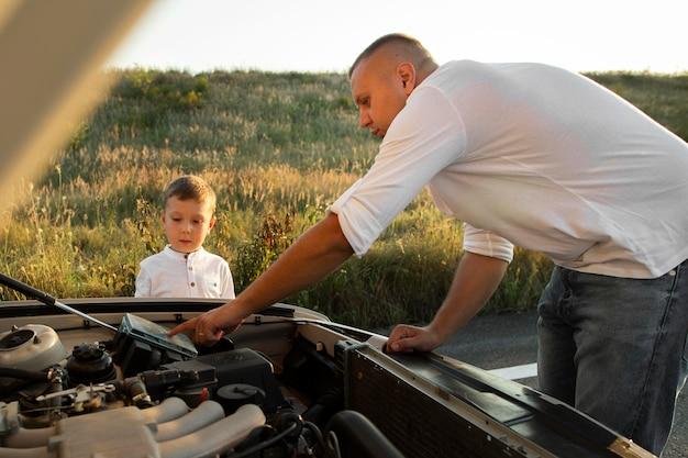 Homem de tiro médio ensinando criança sobre carro