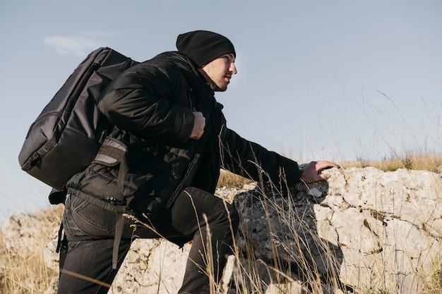 Homem de tiro médio escalando rochas