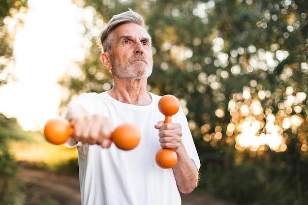Homem de tiro médio fazendo exercícios ao ar livre