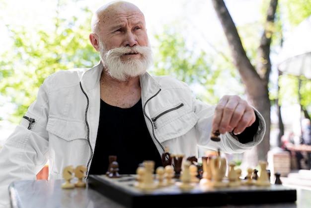 Homem de tiro médio jogando xadrez ao ar livre