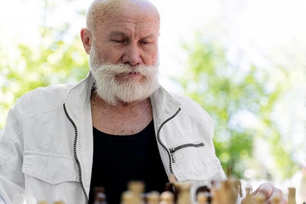 Homem de tiro médio jogando xadrez