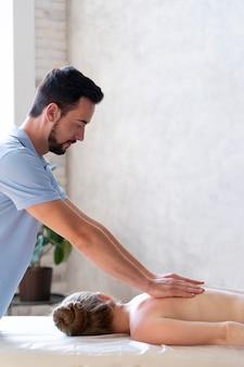 Homem de tiro médio massageando as costas