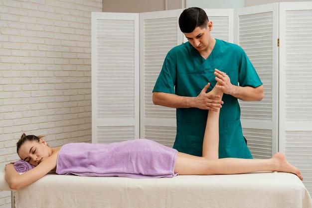 Homem de tiro médio massageando pé