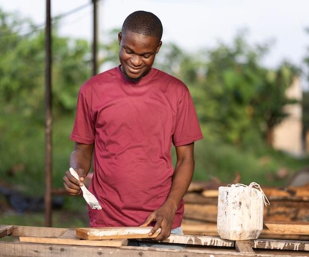 Homem de tiro médio pintando madeira
