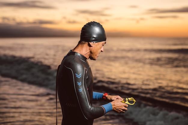 Homem de tiro médio posando à beira-mar
