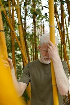 Homem de tiro médio posando com bambu