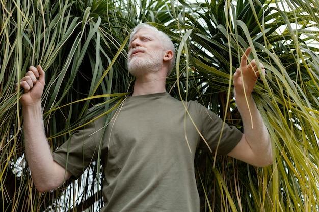 Homem de tiro médio posando com planta