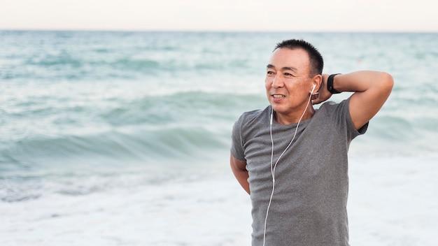Homem de tiro médio se alongando na praia