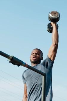 Homem de tiro médio segurando peso