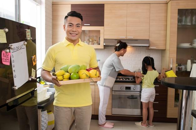 Homem de tiro médio segurando um prato de frutas
