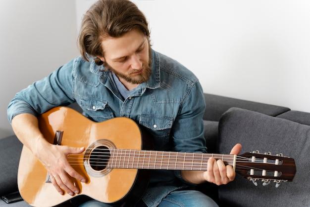 Homem de tiro médio tocando guitarra no sofá
