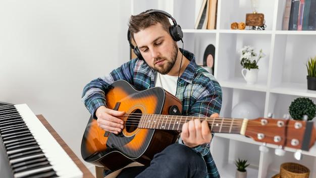Homem de tiro médio tocando música