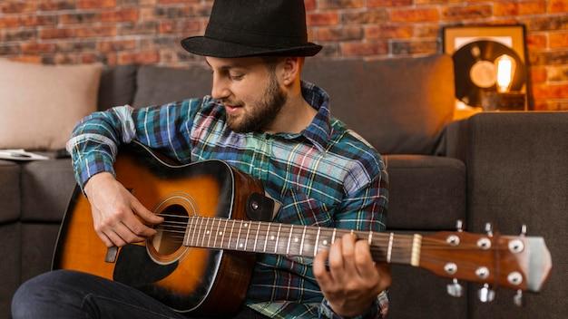 Homem de tiro médio tocando violão dentro de casa