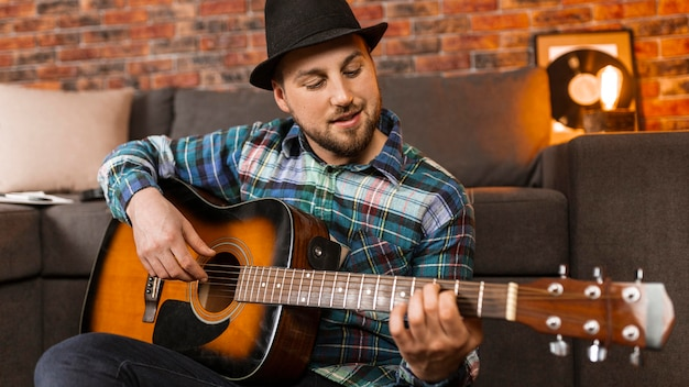 Homem de tiro médio tocando violão