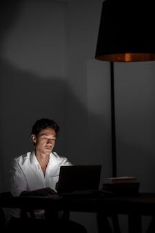 Homem de tiro médio trabalhando à noite