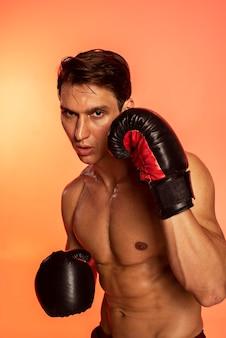 Homem de tiro médio treinando com luvas de boxe