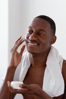 Homem de tiro médio usando creme facial