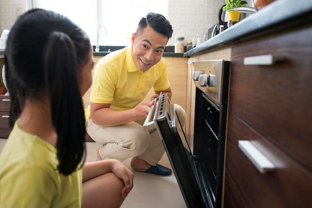 Homem de tiro médio verificando o forno