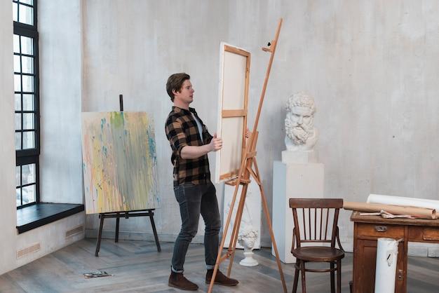 Homem de tiro no escuro, colocando sua pintura em um cavalete