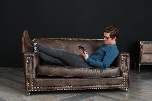 Homem de tiro no escuro, segurando seu tablet enquanto fica no sofá