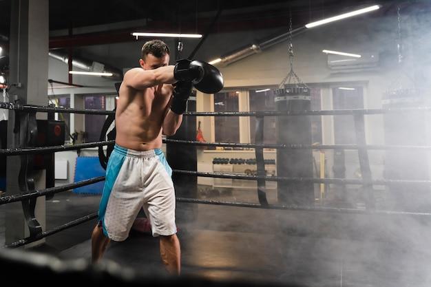 Homem de tiro no escuro treinamento no ringue de boxe