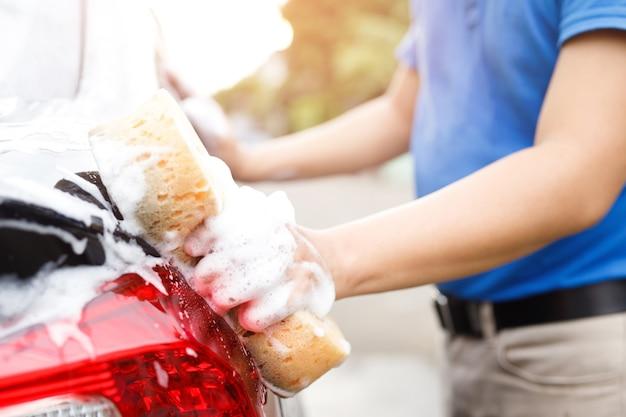 Homem de trabalhador de pessoas segurando a esponja amarela de mão e a janela do limpador de espuma de espuma para lavar o carro. lavagem de carros conceito limpa. deixe espaço para escrever mensagens.