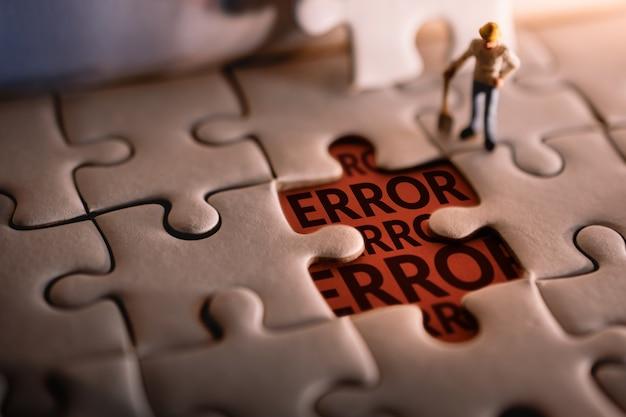 Homem de trabalhador em miniatura encontrou a mensagem de erro em uma peça de quebra-cabeça