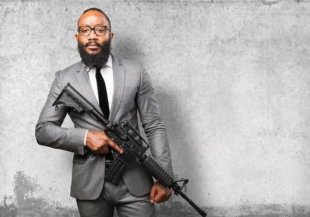 Homem de traje com uma metralhadora