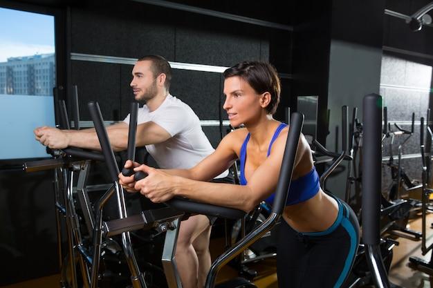Homem de treinador elíptico walker e mulher no ginásio preto